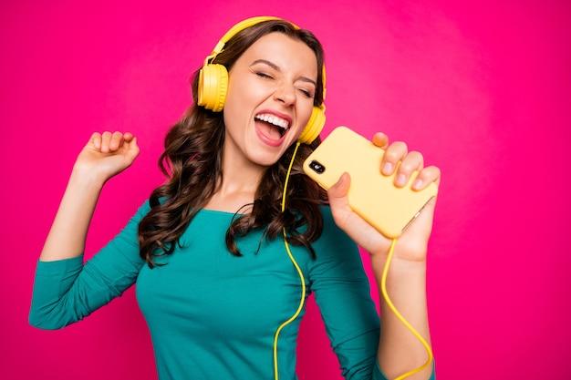 Foto van vrolijke positieve mooie krullende golvende jongere schreeuwen in denkbeeldige microfoon telefoon geïnspireerd door favoriete rockband zingen geïsoleerde levendige kleuren achtergrond