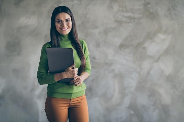 Foto van vrolijke positieve mooie laptop van de vrouwenholding met handen die toothily glimlachen geïsoleerd dichtbij lege ruimte door grijze muur concrete achtergrond