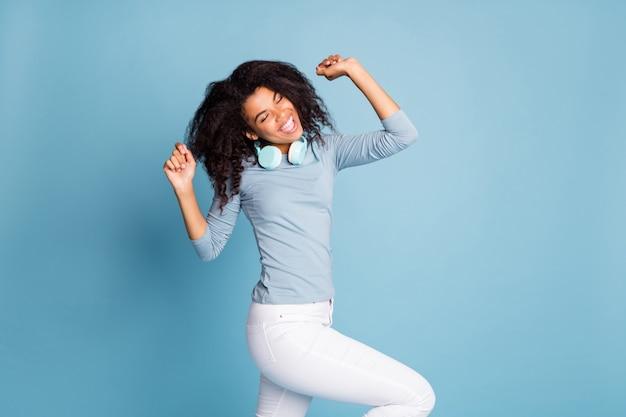 Foto van vrolijke positieve mooie mooie vriendin dansen in witte broek ogen gesloten geïsoleerde pastel blauwe kleur achtergrond