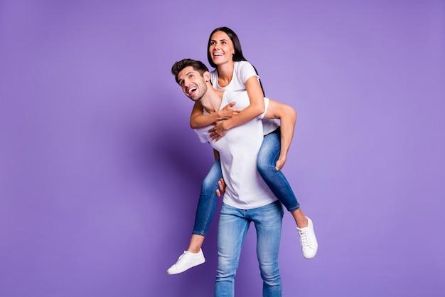 Foto van vrolijke positieve schattig vrij opgewonden modieus paar meeliften meisje knuffelen kerel uitvoering in t-shirt shite denim geïsoleerde pastel violette kleur achtergrond