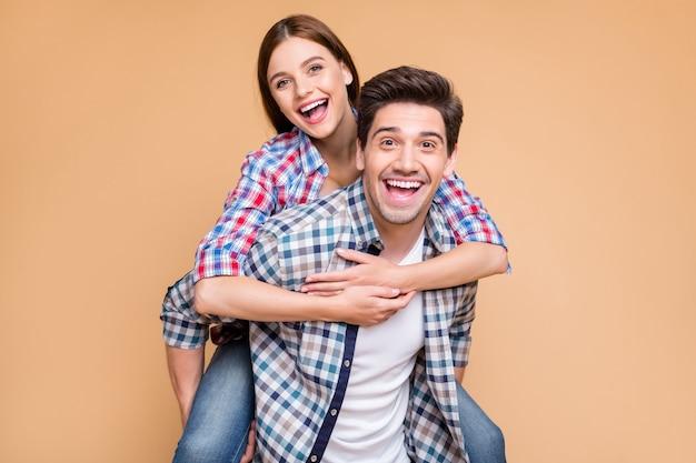 Foto van vrolijke positieve schattige charmante fascinerende aardige vriendin en vriend met haar die zijn rug heeft gereden en hij houdt haar het dragen van spijkerbroek denim geïsoleerd over beige pastel kleur achtergrond