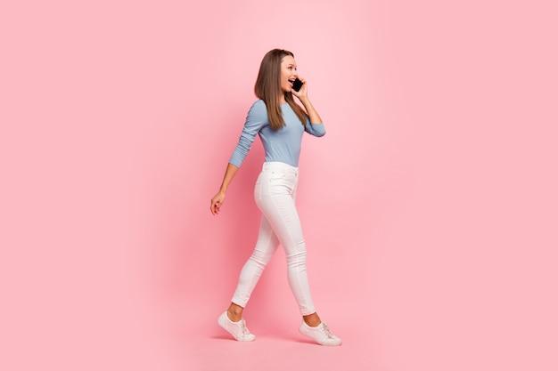 Foto van vrolijke positieve vriendin in gesprek met haar vrienden aan de telefoon in witte sneakers geïsoleerd onderweg over pastel kleur achtergrond
