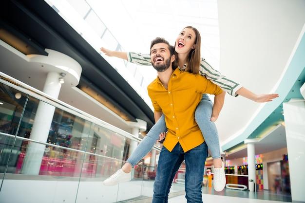 Foto van vrolijke schattige dame spreidde armen als vleugels knappe kerel draagt haar mee op de rug bezoek winkelcentrum winkelcentrum samen goed humeur plezier hebben ontmoet avonturen draag casual outfit binnenshuis