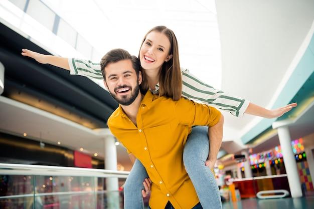 Foto van vrolijke schattige dame spreidde armen als vleugels, knappe kerel draagt haar mee op de rug bezoek winkelcentrum winkelcentrum samen goed humeur plezier spelen dragen casual outfit binnenshuis