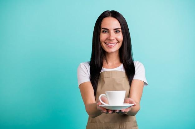 Foto van vrolijke schattige mooie charmante vrouw server geven u kopje heerlijke koffie glimlachend toothily geïsoleerde groenblauw levendige achtergrond kleur