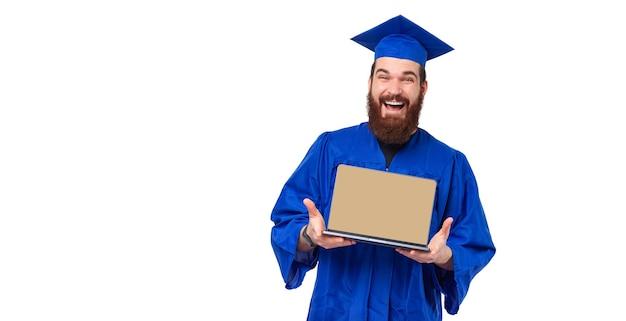 Foto van vrolijke studentenmens in blauw gewaad die laptop het scherm toont