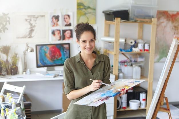 Foto van vrolijke succesvolle jonge vrouwelijke kunstenaar, met palet en penseel, afwerking van het grote schilderij. mensen en werk