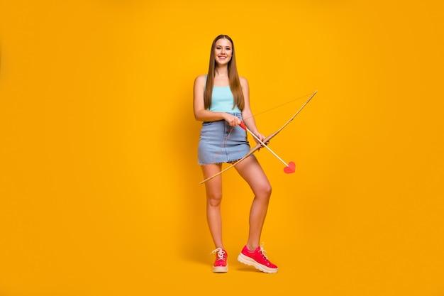 Foto van vrolijke tiener die stapel pijlen in handen houdt die over gele achtergrond worden geïsoleerd