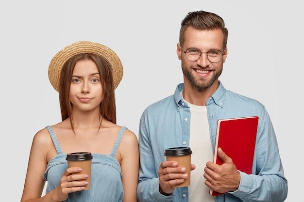 Foto van vrolijke tienervriend heeft koffiepauze na het studeren, houdt wegwerpbekers drank vast