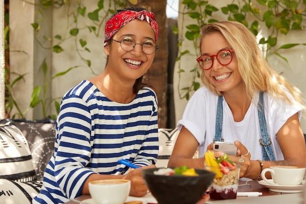 Foto van vrolijke twee gemengde rasstudenten ontmoeten elkaar in café voor het voltooien van een gemeenschappelijke taak, genieten van een smakelijk gerecht, glimlachen breed, dragen een optische bril, chatten op mobiele telefoon, schrijven oefening in notitieblok, drinken koffie