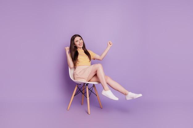 Foto van vrolijke verbaasde winnaar meisje zit stoel viert overwinning op violette achtergrond