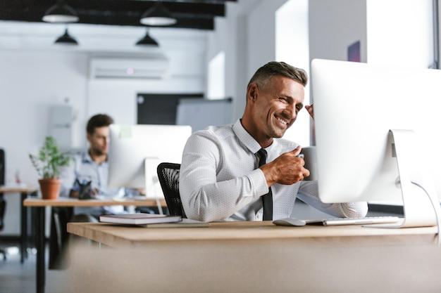 Foto van vrolijke volwassen man 30s dragen wit overhemd en stropdas drinken thee uit beker, zittend door de computer op kantoor