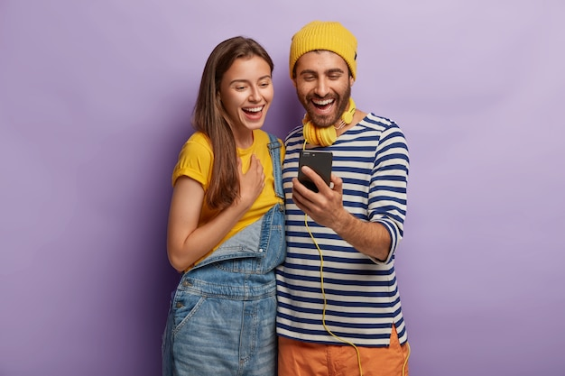 Foto van vrolijke vrienden die samen vrije tijd doorbrengen, iets op smartphone kijken, dicht bij elkaar staan