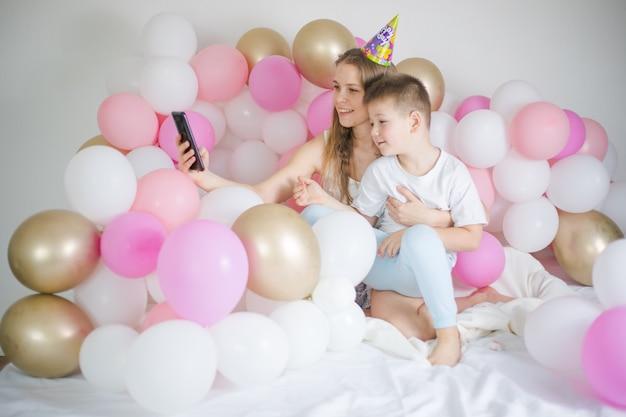 Foto van vrolijke vrouw met jongen jongen glimlachend en selfie foto op mobiel met ballon
