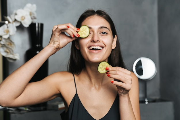 Foto van vrolijke vrouw met lang donker haar en een gezonde huid komkommer op het gezicht zetten