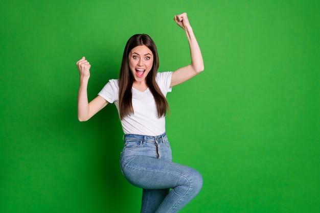 Foto van vrolijke winnaar vrouw gekleed casual outfit armen omhoog open mond geïsoleerde groene kleur achtergrond