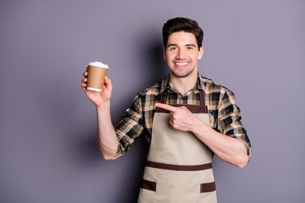 Foto van vrolijke zelfverzekerde aantrekkelijke knappe man wijzend op wegwerp kopje koffie die u dit soort geïsoleerde grijze kleur muur aanbeveelt