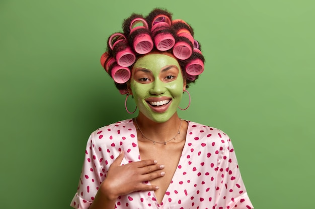 Foto van vrolijke zorgeloze vrouw geniet van het ondergaan van schoonheidsprocedures thuis, draagt een groen gezichtsmasker voor een gezonde huid, draagt haarkrulspelden, gekleed in zijden jurk, hoort iets grappigs, vormt binnen