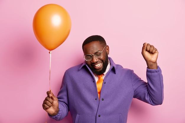 Foto van vrolijke zwarte man werpt gebalde vuist, viert verjaardag, wacht op gasten, dansen met luchtballon, lacht oprecht, gekleed in paarse jas