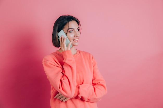 Foto van vrouw die lacht tijdens het praten over smartphone geïsoleerd op roze achtergrond