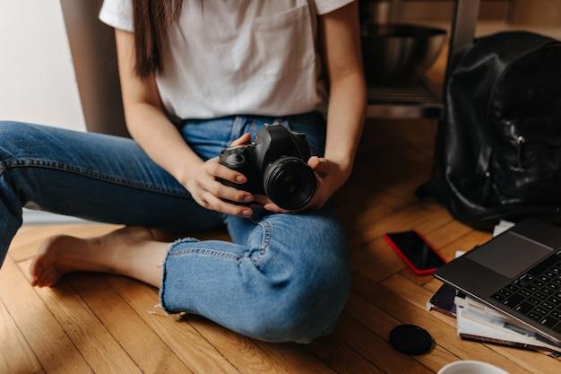 Foto van vrouw in spijkerbroek zittend op de vloer met voorkant, laptop en telefoon