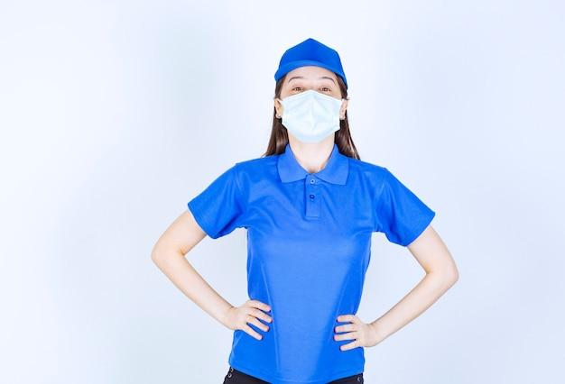 Foto van vrouw in uniform en medisch masker poseren met handen op de heupen.