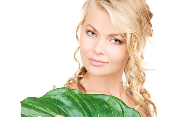 Foto van vrouw met groen blad over wit