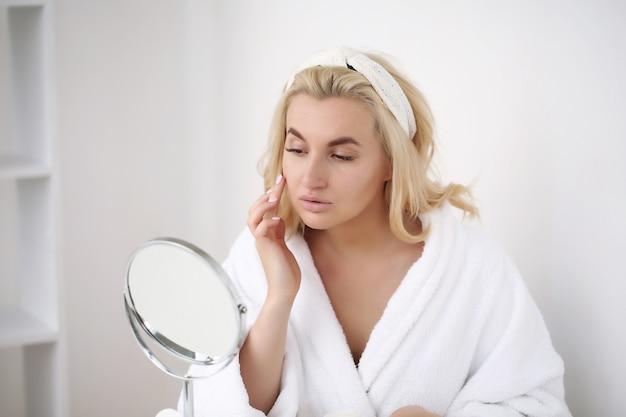 Foto van vrouw na bad in witte badjas en handdoek op wit. huid zorg concept.