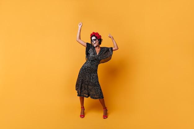 Foto van vrouw vreugdevol schreeuwen en dansen op een oranje achtergrond. meisje in bolletjesjurk met gezichtskunst poseert opgewekt.