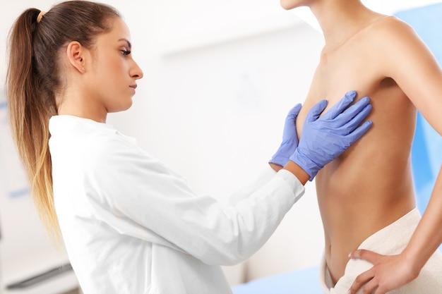 Foto van vrouwelijke arts die borst onderzoekt