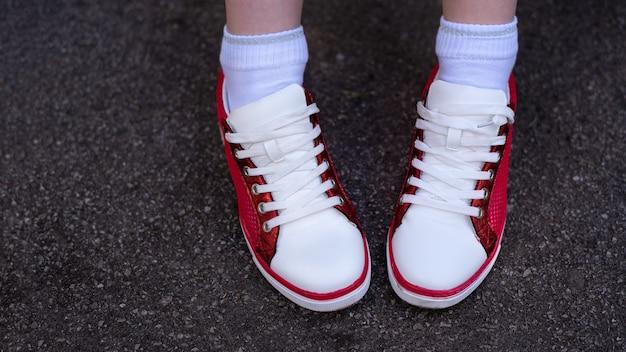 Foto van vrouwelijke benen in rode en witte sneakers op grijs nat asfalt