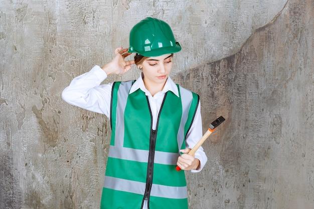 Foto van vrouwelijke bouwvakker in groene helm met hamer
