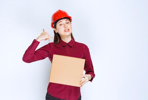 Foto van vrouwelijke ingenieur in rode helm met kartonnen doos op witte achtergrond.