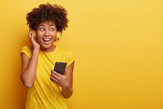 Foto van vrouwelijke meloman luistert favoriete afspeellijst in koptelefoon