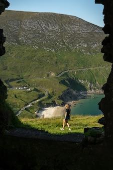 Foto van vrouwelijke reiziger in keem bay achill island ireland door een raam van een oud gebouw