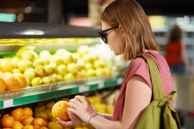 Foto van vrouwelijke tiener staat achteruit, draagt rugzak op rug, kiest sinaasappels voor het maken van fruitsalade, draagt tinten, houdt zich aan gezonde voeding, poseert in supermerket. mensen en inkoopconcept