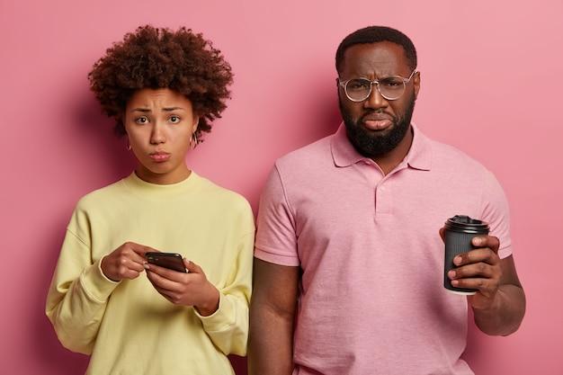 Foto van wanhopig nors afro-amerikaans echtpaar leest slecht nieuws in sociale netwerken, drinkt afhaalkoffie, trieste vrouw wijst op display van smartphone