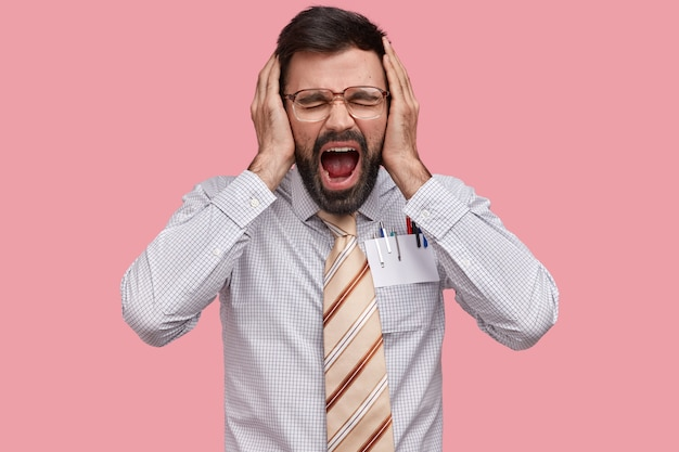 Foto van wanhopige geërgerd bebaarde man houdt handen op het hoofd, schreeuwt luid, houdt de handpalmen op de oren, opent de mond, sluit de ogen, voelt zich depressief