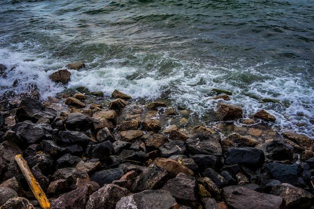 Foto van water dat een rotsachtige kust raakt