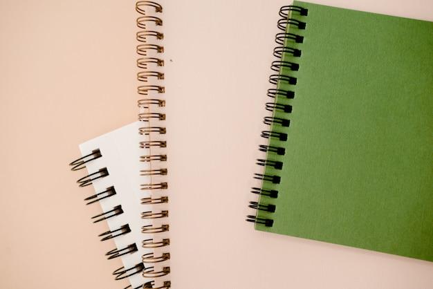 Foto van werkruimtebureau met witte en groene notitieboekjes minimale stijl.