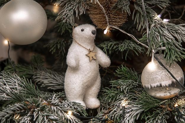 Foto van witte teddybeer zittend op kerstboom in sneeuw, kerstboomdecor, feestelijk concept, lichten, kerstballen