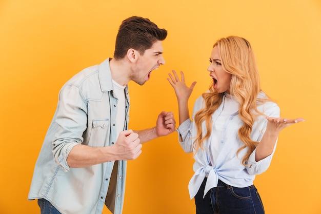 Foto van woedende man en vrouw in denimkleren die tegen elkaar schreeuwen die zich van aangezicht tot aangezicht bevinden, geïsoleerd over gele muur