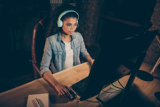 Foto van zakelijke dame kijkt groot scherm overuren gebruik oortelefoons