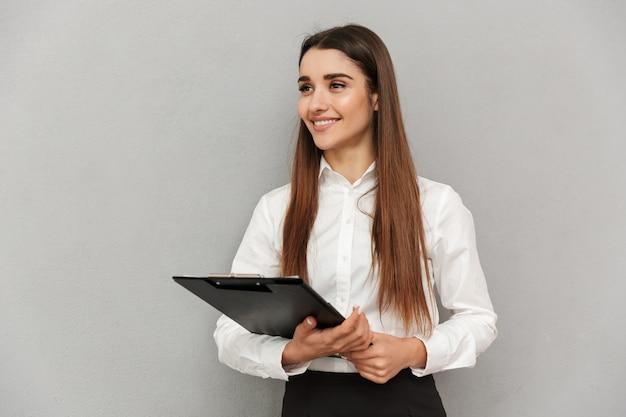 Foto van zakelijke gelukkige vrouw in wit overhemd en zwarte rok met klembord met bestanden in kantoor en opzij kijken op copyspace, geïsoleerd over grijze muur