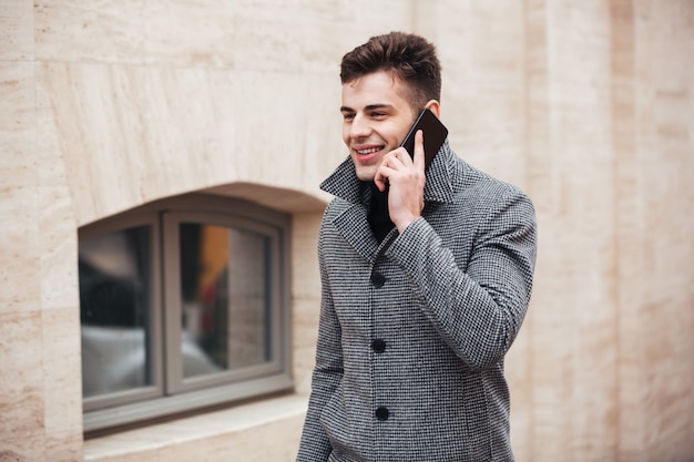 Foto van zakelijke man in jas op straat lopen, en met mobiel gesprek