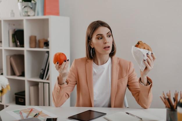 Foto van zakenvrouw in roze jasje zittend op de werkplek. vrouw kiest tussen smakelijke hamburger en gezonde appel.