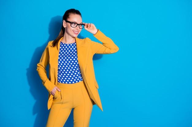 Foto van zelfverzekerd cool mooi prachtig prachtige dame baas kijk copyspace klaar beslissen werk beslissing aanraking bril draag gele broek broek geïsoleerde blauwe kleur achtergrond