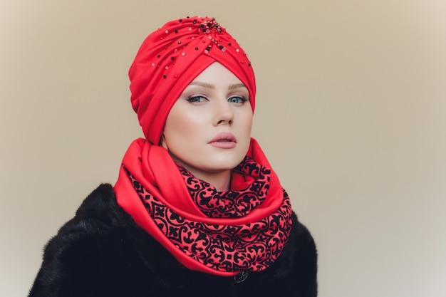 Foto van zelfverzekerde arabische dame in hijab, toont je de goede weg, wijst met beide vingers naar de lege ruimte, nodigt uit om daarheen te gaan, promots kopiëren de ruimte. bekijk het met mij eens.