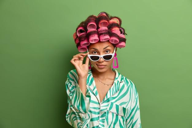 Foto van zelfverzekerde donkere vrouw kijkt van een zonnebril, heeft zelfverzekerde blik, luistert aandachtig naar iemand, maakt perfecte krullen met haarkrulspelden, bereidt zich voor om een speciale gelegenheid in het leven te vieren