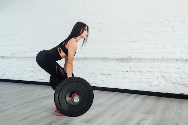 Foto van zelfverzekerde jonge vrouw gewichtheffen training bij sportschool terug te draaien.